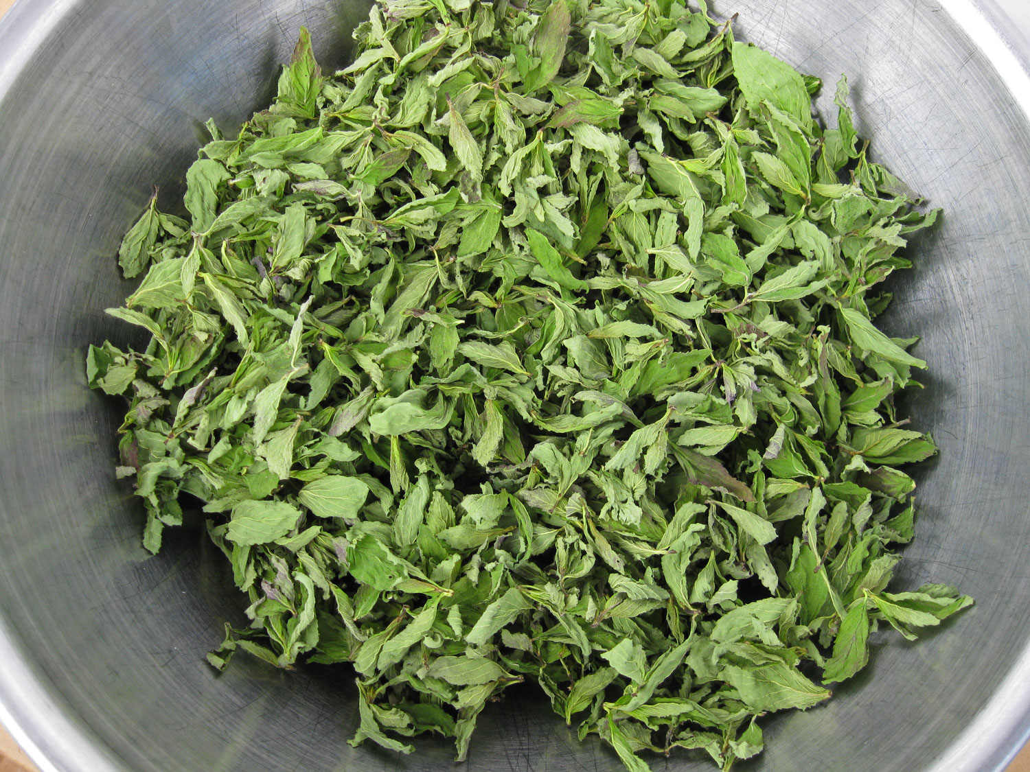 If the mint is handled well and dried quickly then it will retain some of the green color.