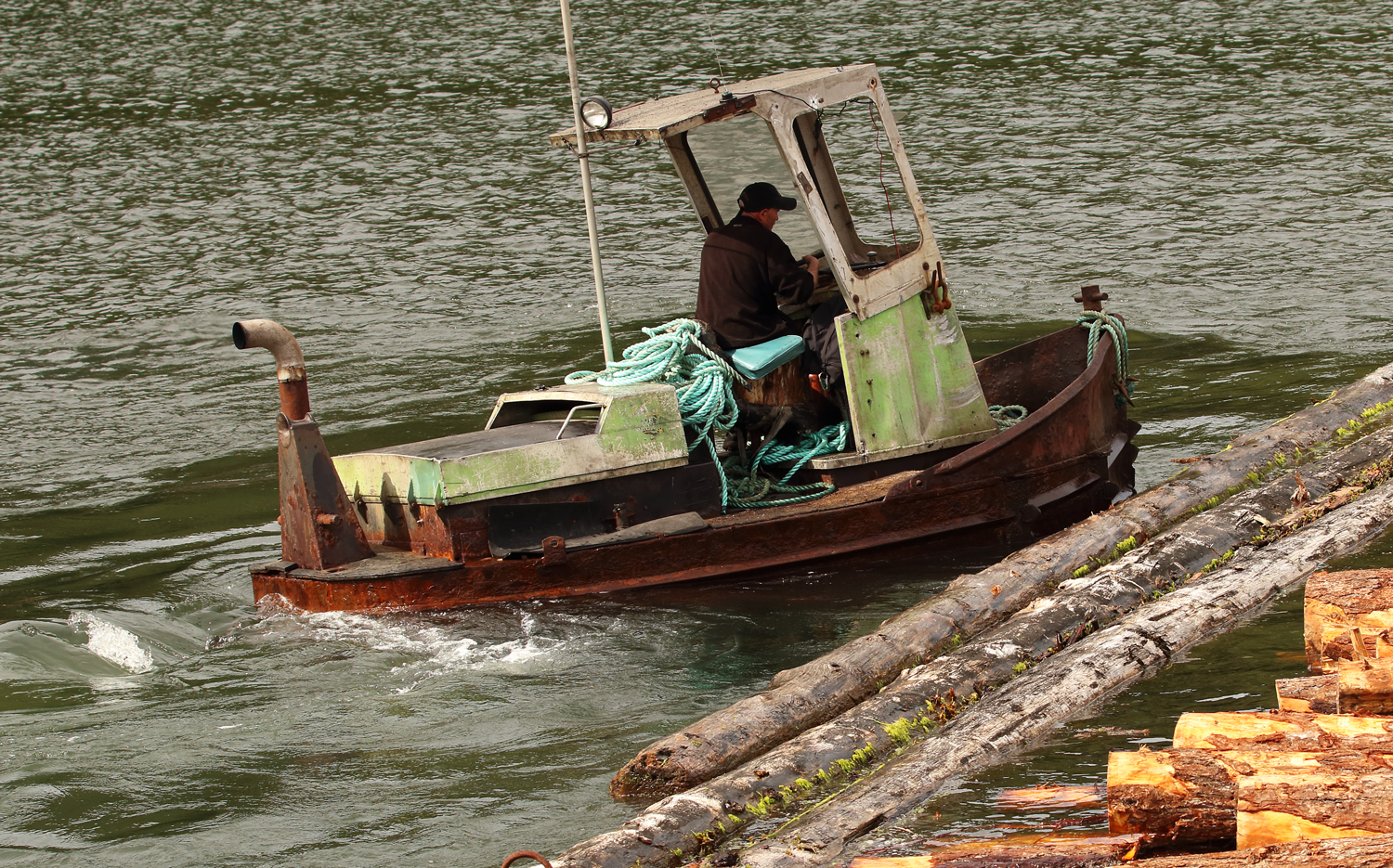 Log bronc boom boat working boom sticks by Prince of Wales Island in Southeast Alaska