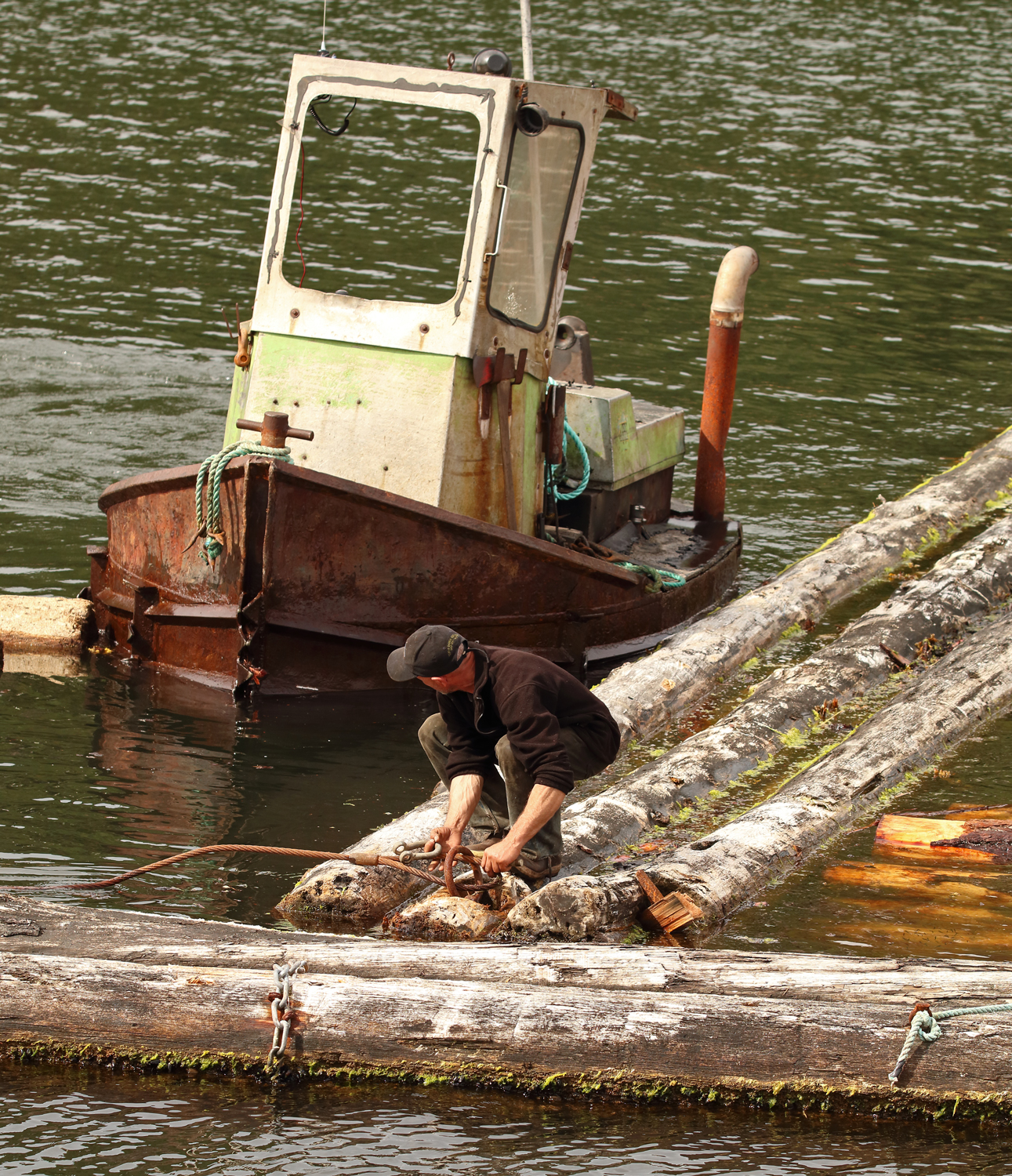 Boom man watching boat while handling shackle Prince of Wales Island Southeast Alaska
