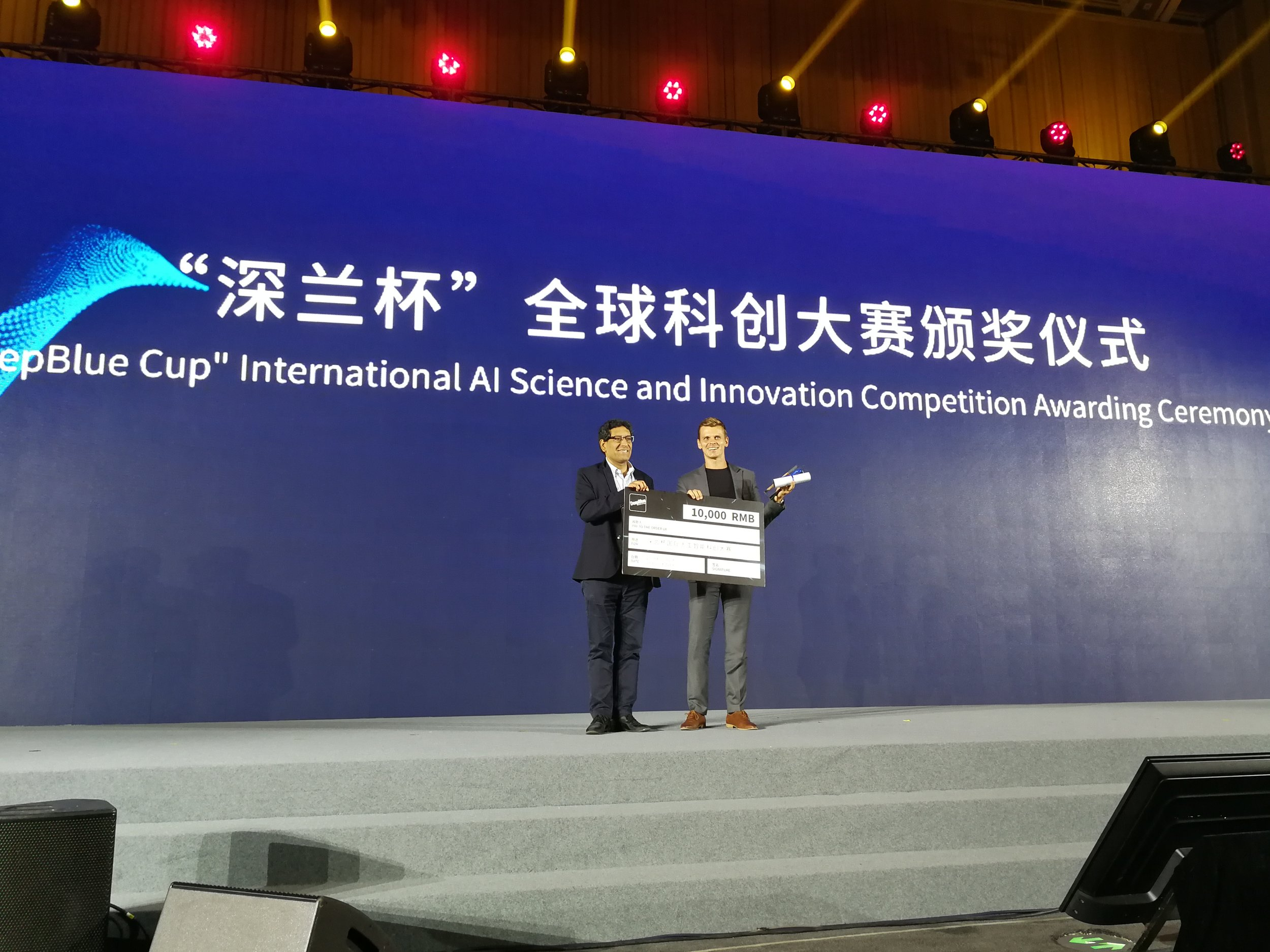 Matt Morawski holding the 10,000 RMB check and the winning certificate.