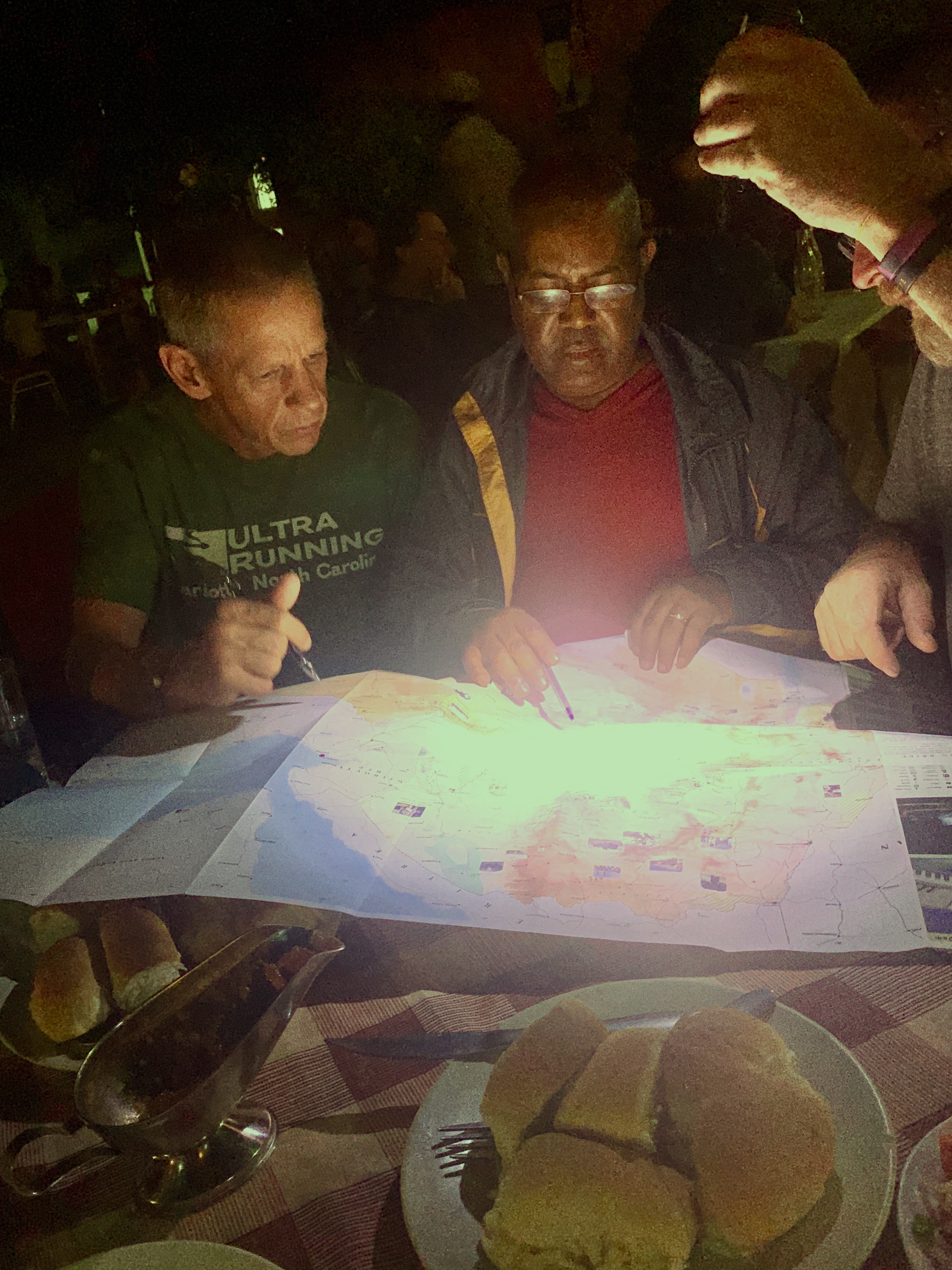 One of many late night map sessions with my team. Solomon is giving us his thoughts on the route, based on his local expertise.