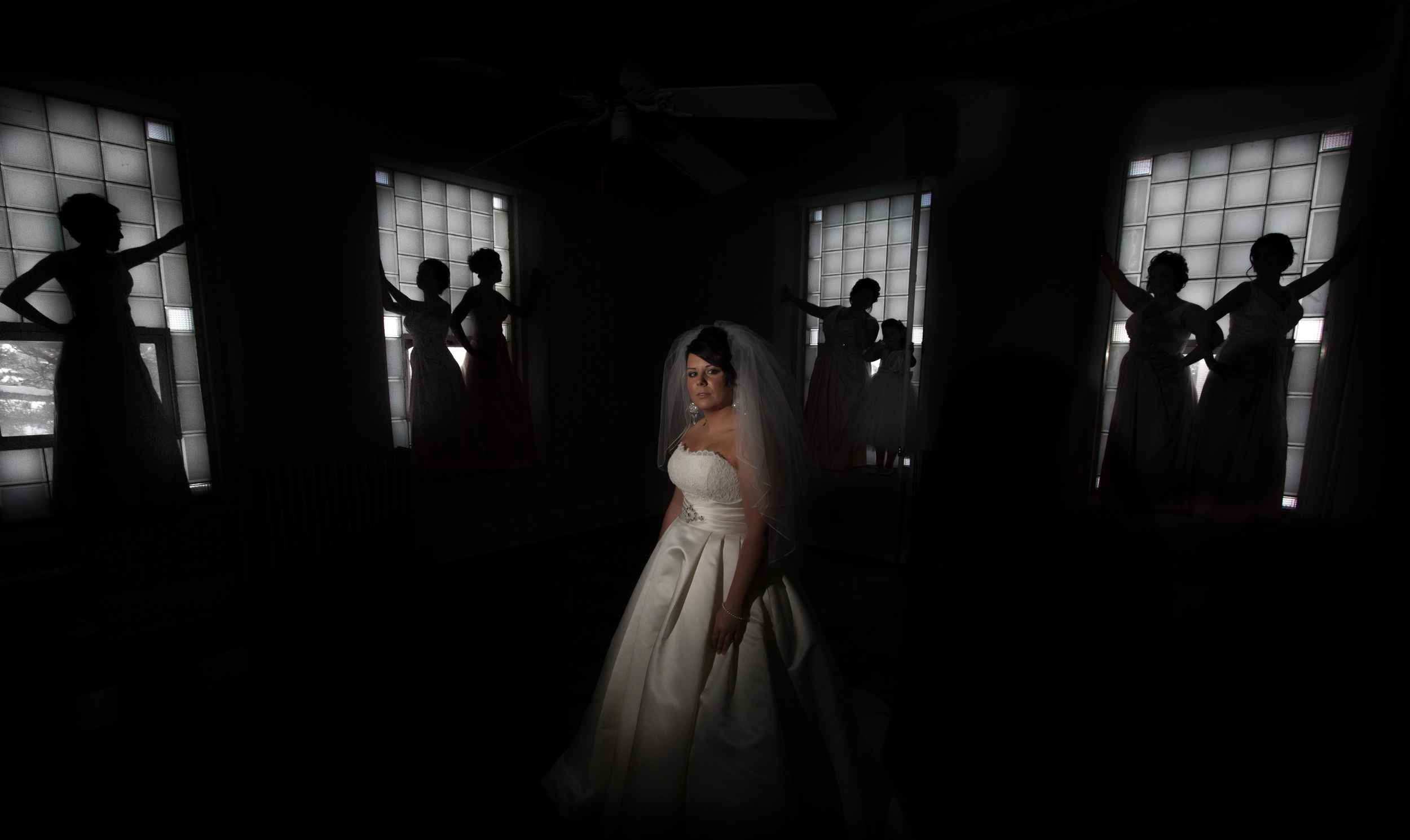 Caitlyn (Morris) Meitner poses prior to her wedding as herbridesmaidsstrike a pose, silhouetted against the windows of an old classroom.