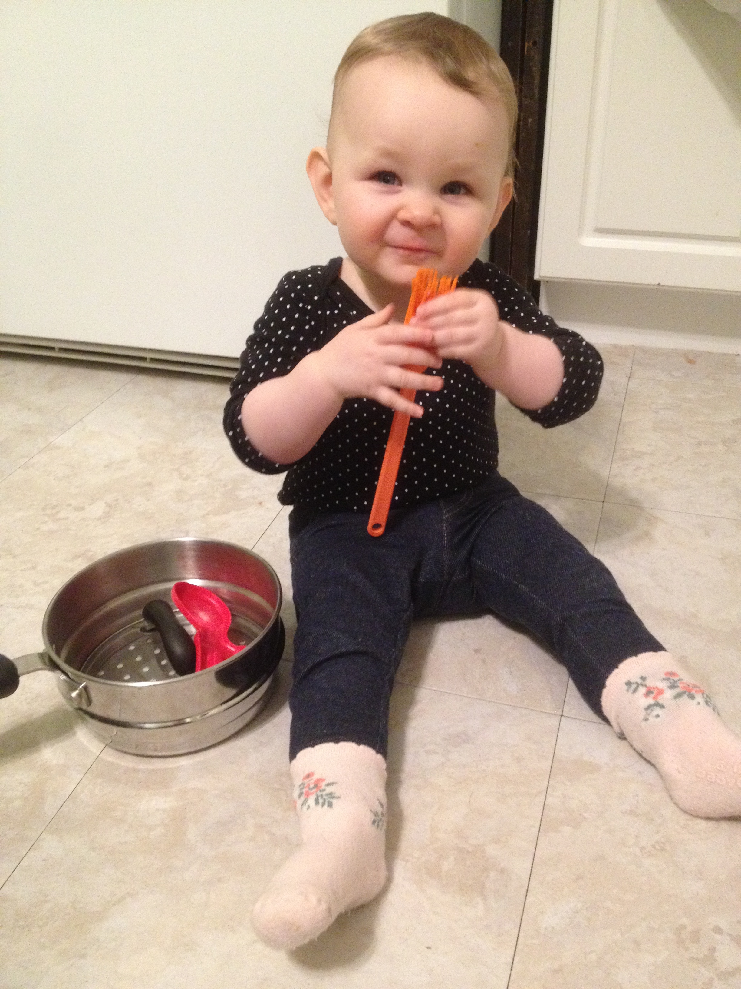 Playing with pots and random kitchen items while I do some dishes. Soon after this she learned to crawl and was barred from our kitchen so she wouldn't fall down the stairs. In the new house the basement stairs have a door - so excited for that!