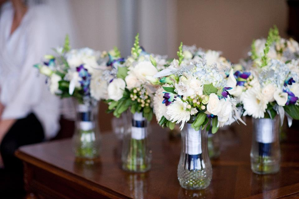 the bridesmaids bouquets were full and lush, filled with blue and white flowers and silver holiday greens