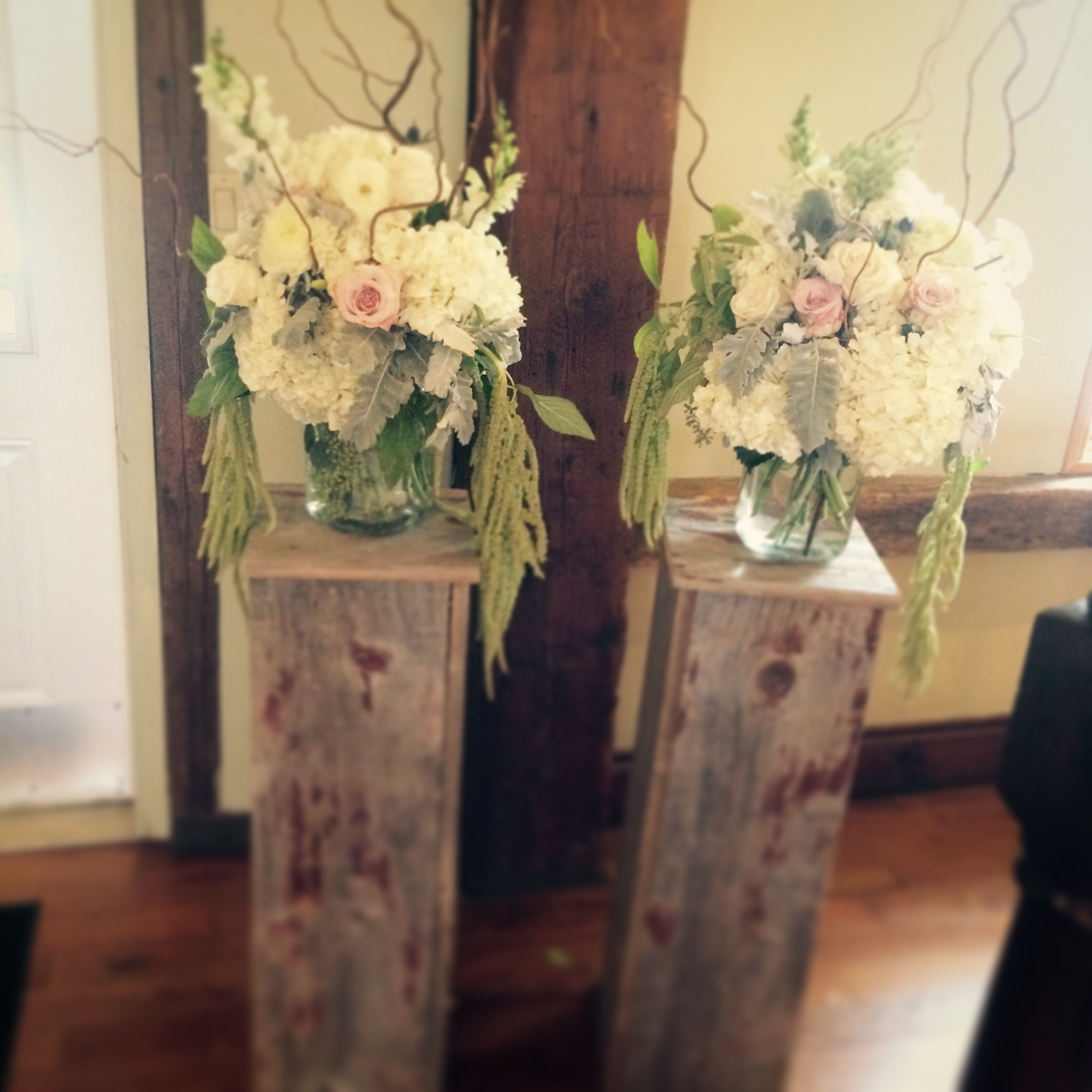 """These authentic barn board pedestals are the perfect height for your ceremony flower décor at your altar. They can then be moved into the reception area and placed on either side of your head table.  Standing roughly 40"""" tall."""