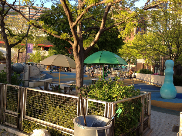 The is the nearby kids' run/play area, with tables, umbrellas, and a giant smurf buttplug.