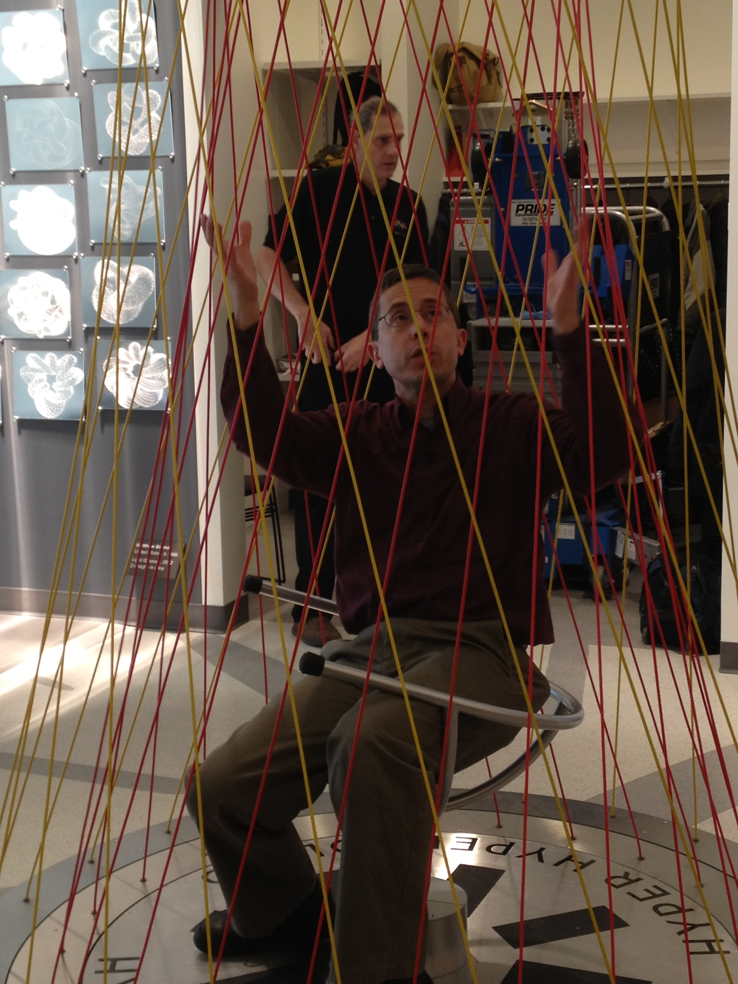 Executive director Glen Whitney demos the hyperboloid chair, which invites visitors to sit in the rotating chair and watch straight lines form a curved shape; think of a  cooling tower.