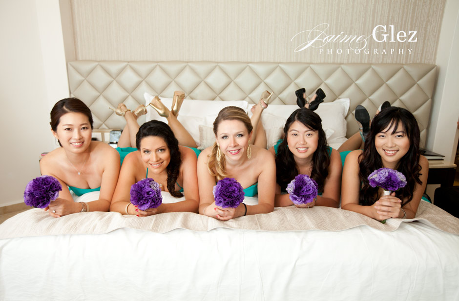 Bridesmaids wearing turquoise dresses and purple bouquets. Ideal outfit for a beach wedding.