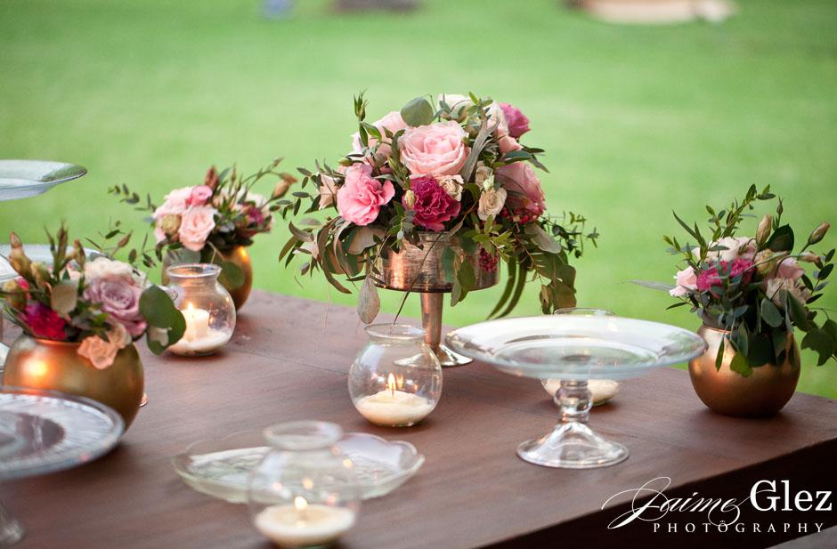 Pequeños y frescos bouquets de rosas en las mesa de postres.