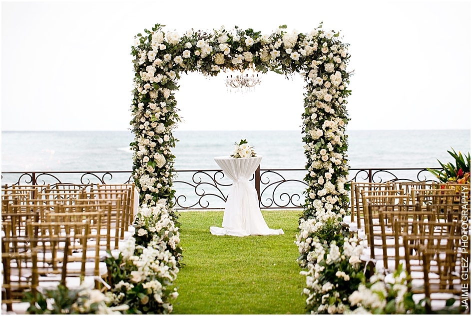 Lovely white floral beach wedding arch decoration.