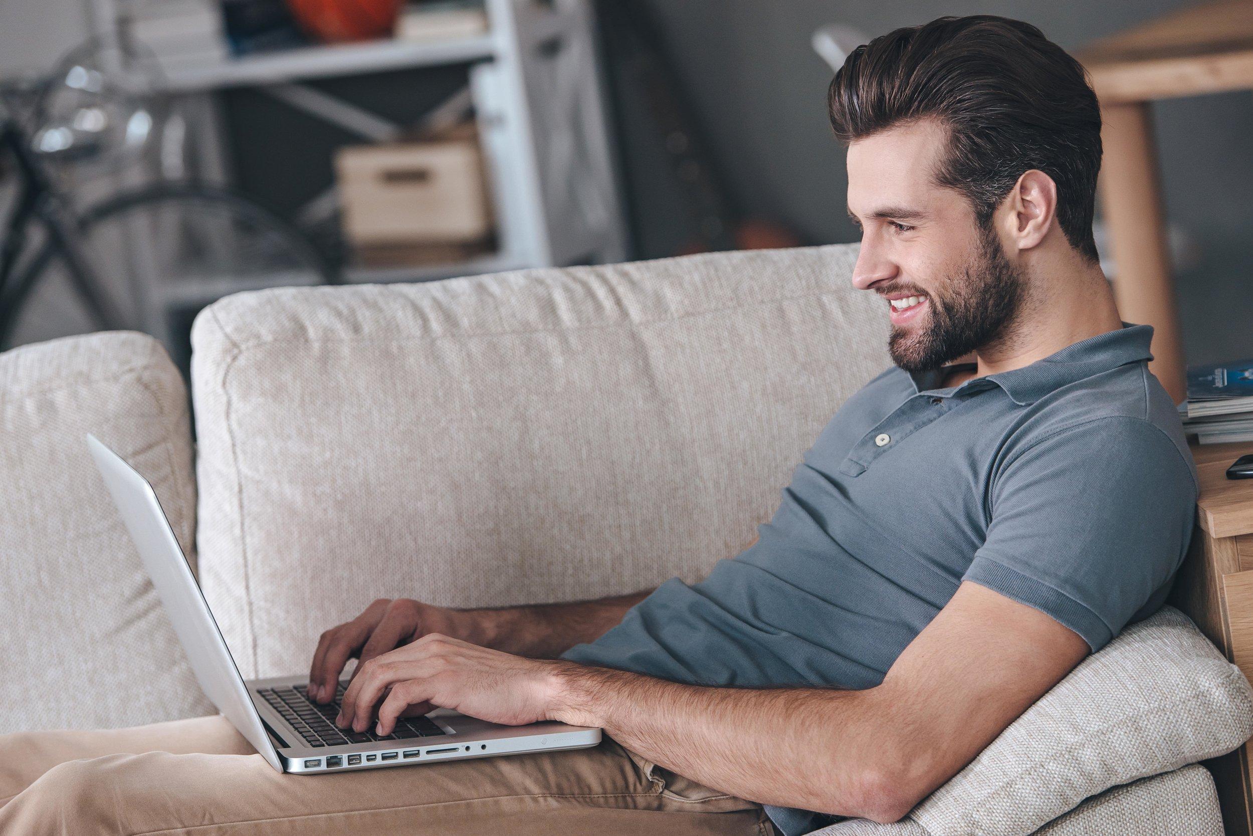 Man on sofa on laptop video chat-min.jpg