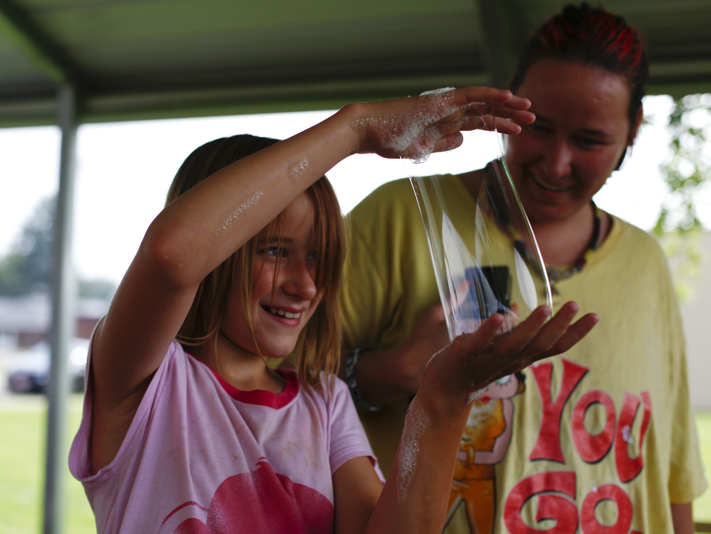 Miya Powell, 9 of Uniontown, Ky., laughs with her mother as she tries to make a large bubble with her hands.