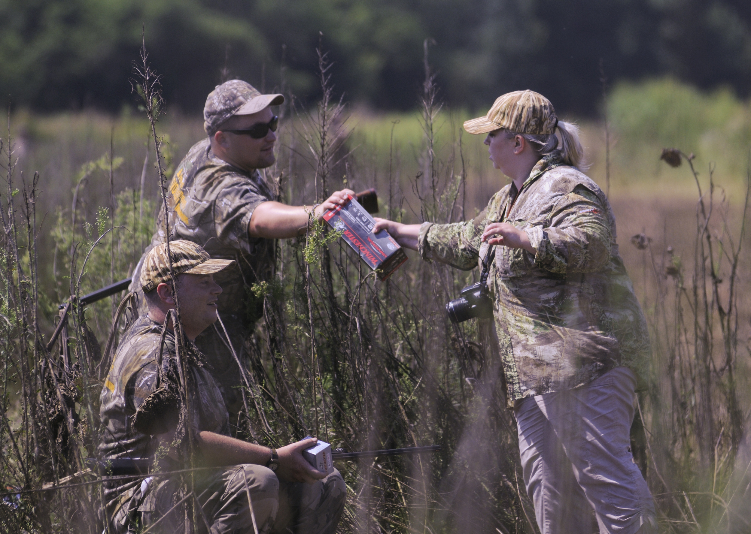Katrina Coffelt hands shells to Kris Boswell during the opening day of dove season. Coffelt is one of the many volunteers who helped make the weekend possible.