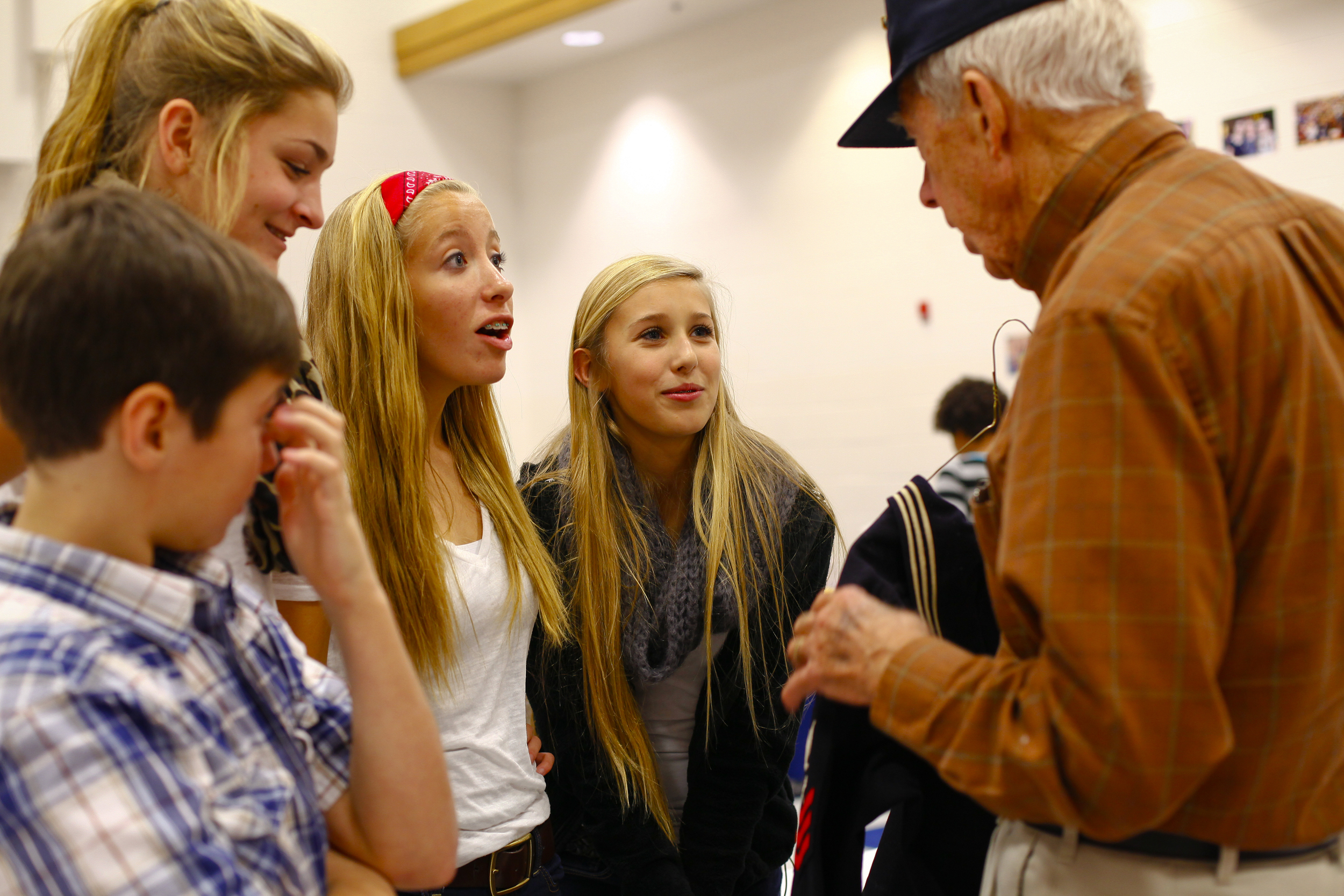 Eighth grade ambassadors Tristan Henson,left, Madelyn Burgess, Lauren Hardesy, and Ashley Spillman speaks with Navy retiree Orville Bryant about his uniform.