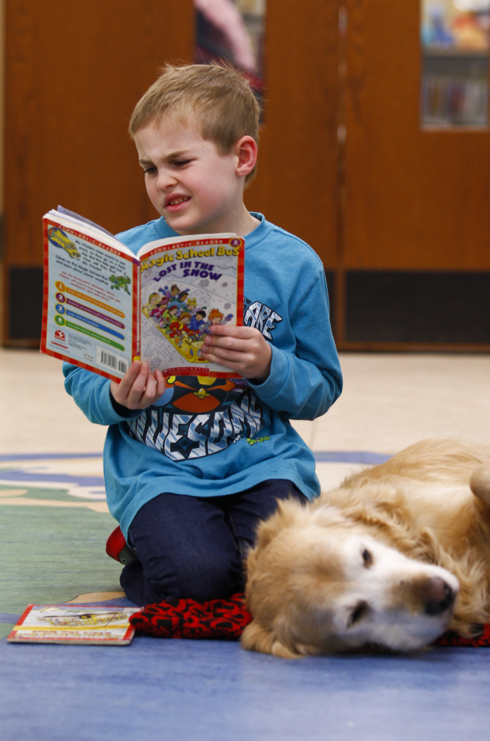 Trey McGonnell, 7 of Crestwood, reads to Doc during the PAWs to Read Program at the Oldham County Library. The program allows children to read aloud to a therapy dog to help improve their reading skills. Doc is one of six volunteer dogs that the program utilizes.