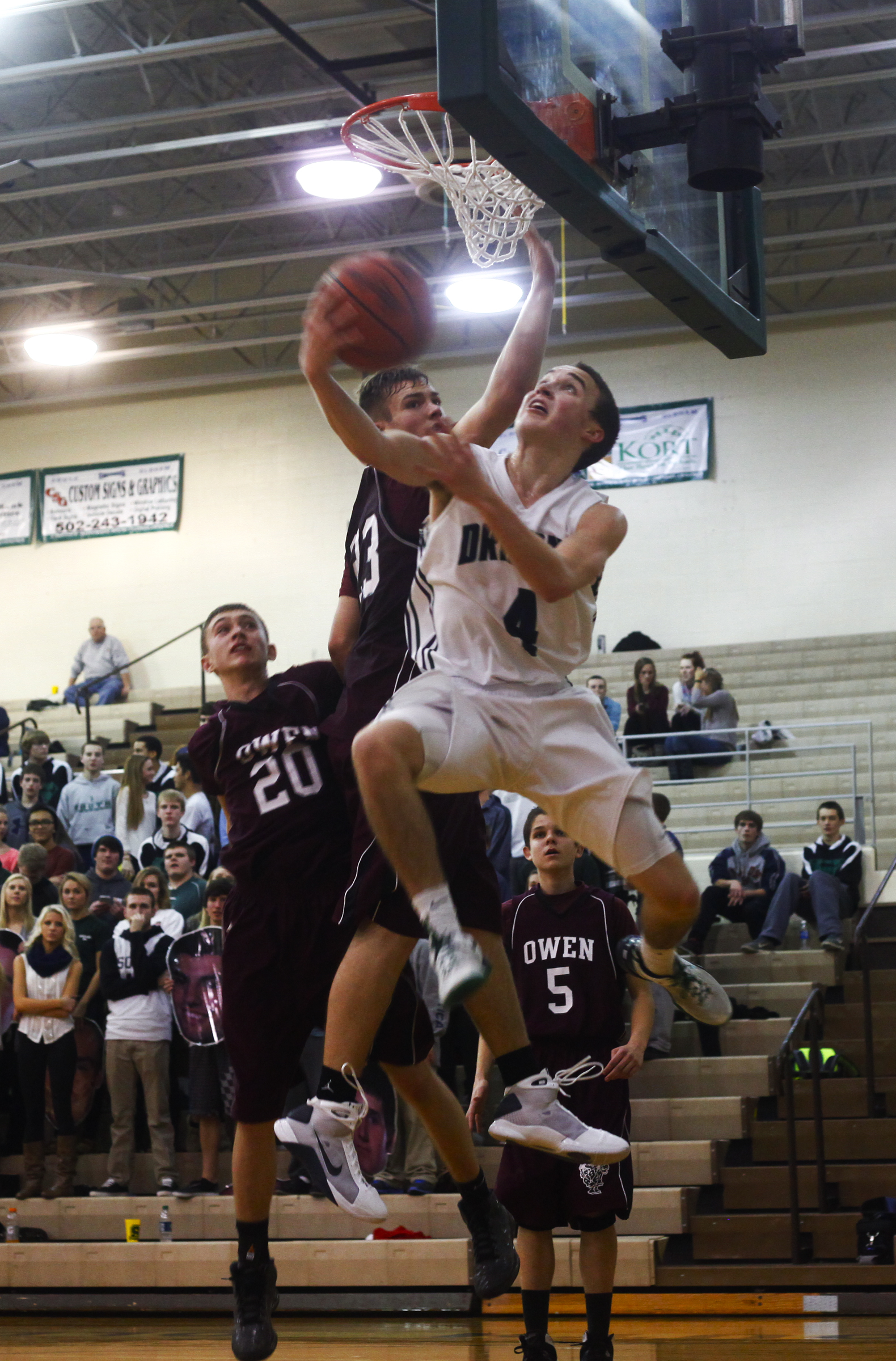 South Oldham guard Michael Griffin makes a reverse layup against Owen County sophomore guard Carson Williams during their 82 - 70 win against Owen on February 15 in Crestwood.