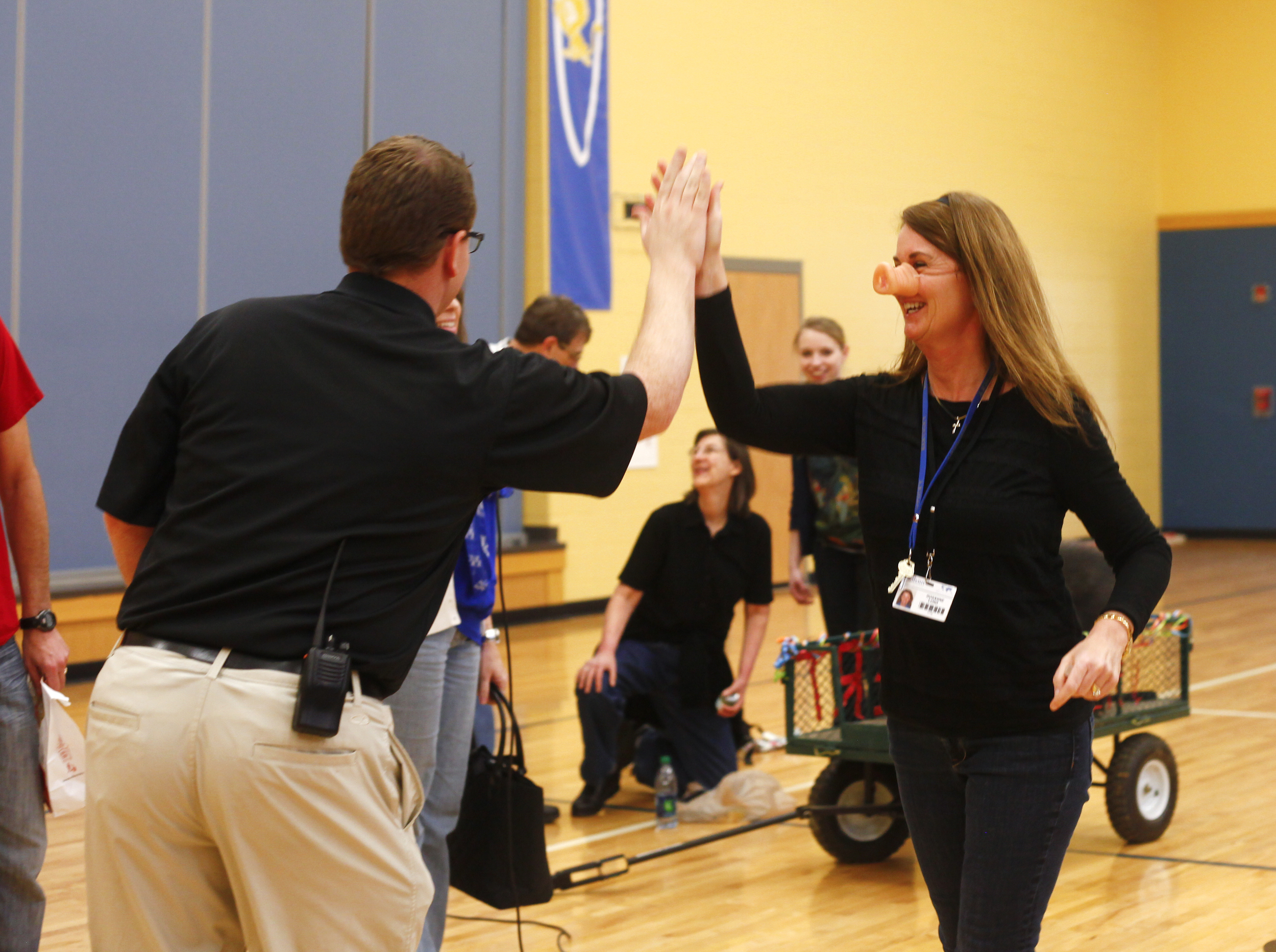 Third grade teacher Roxanne Lund high fives Principal Andy Moore after being called down to kiss Herbert the pig.