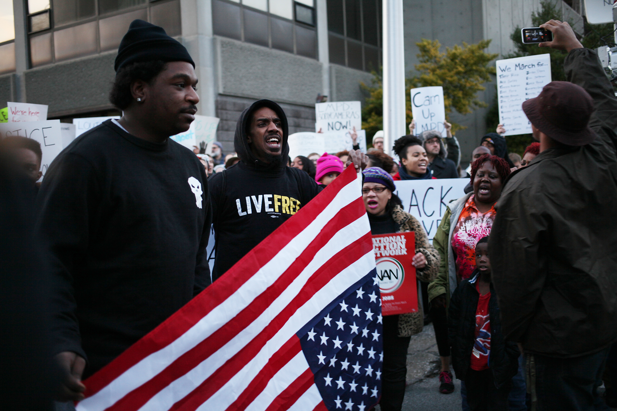 Community members gathered outside of Louisville Police Department headquarters to protest for more transparency in police actions after the death of Michael Brown, an unarmed man, in Ferguson. Mo. The protest took place the day after Officer Darren Wilson, who fatally shot Brown, was not indicted.