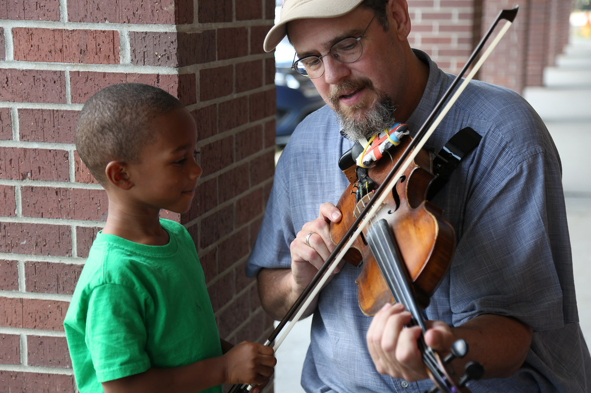 Tom Cunningham explains how he plays the violin at an event that celebrated military families.