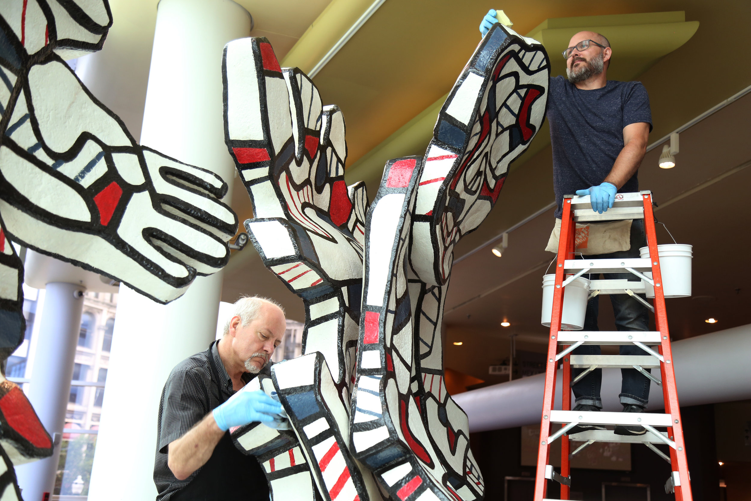 "Conservators from The Conservation Center in Chicago clean ""Faribolus and Perceval"" by Jean DuBuffet."