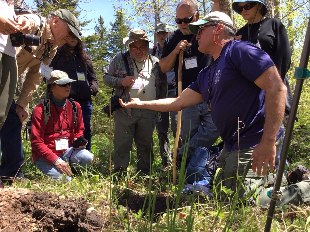 Robert Ayotte showing clay in a soil pit