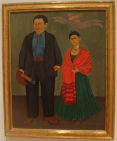Freida was really young here, when she got married to Diego Rivera. The banner says about how happy they are. Plus this is right when she first starts getting into those crazy feminine traditional clothes she was famous for when she was older.