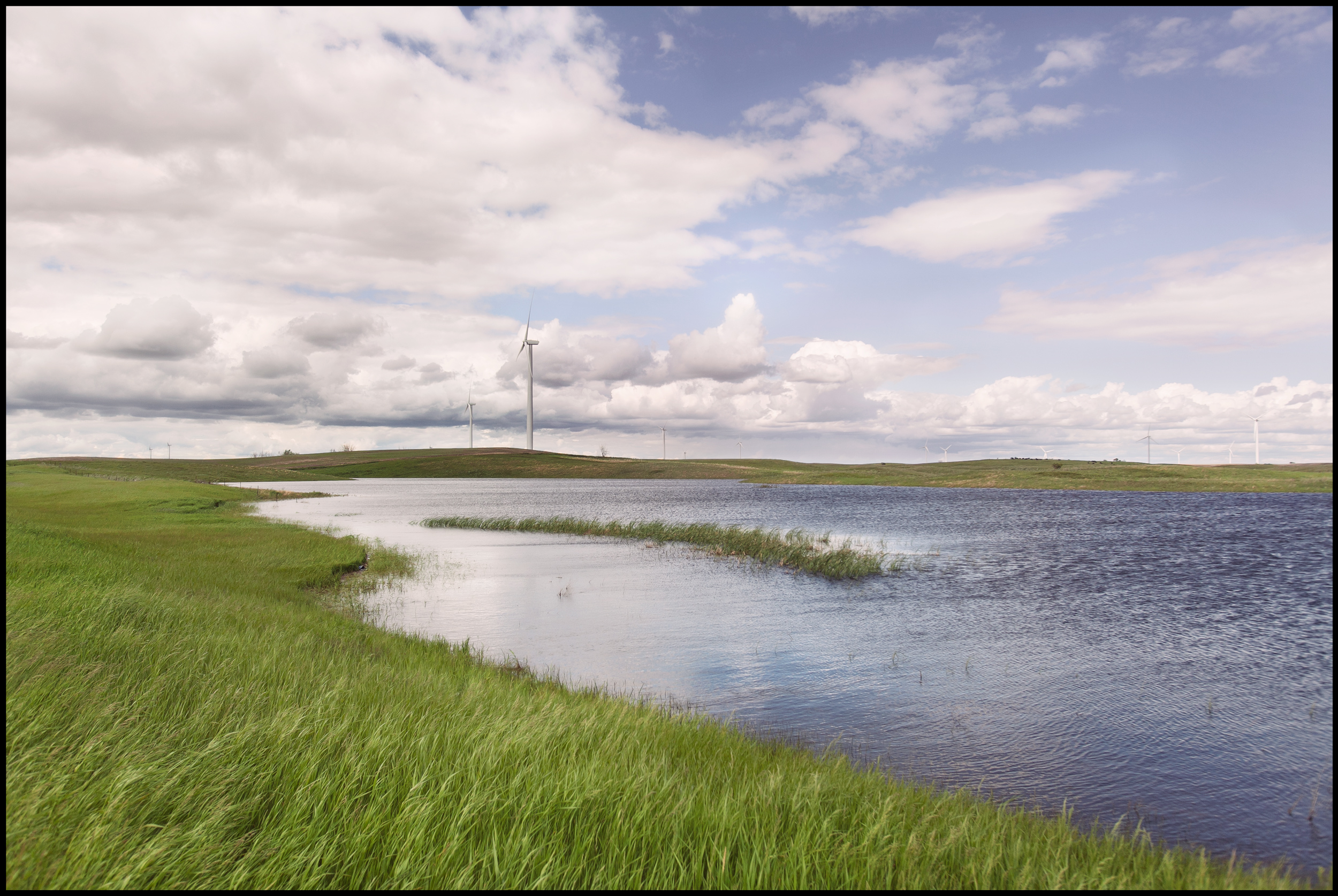 A drive between Bismarck and Minot North Dakota. A long winter and heavy rains have flooded the region and left small lakes scattered through-out the rolling hills.