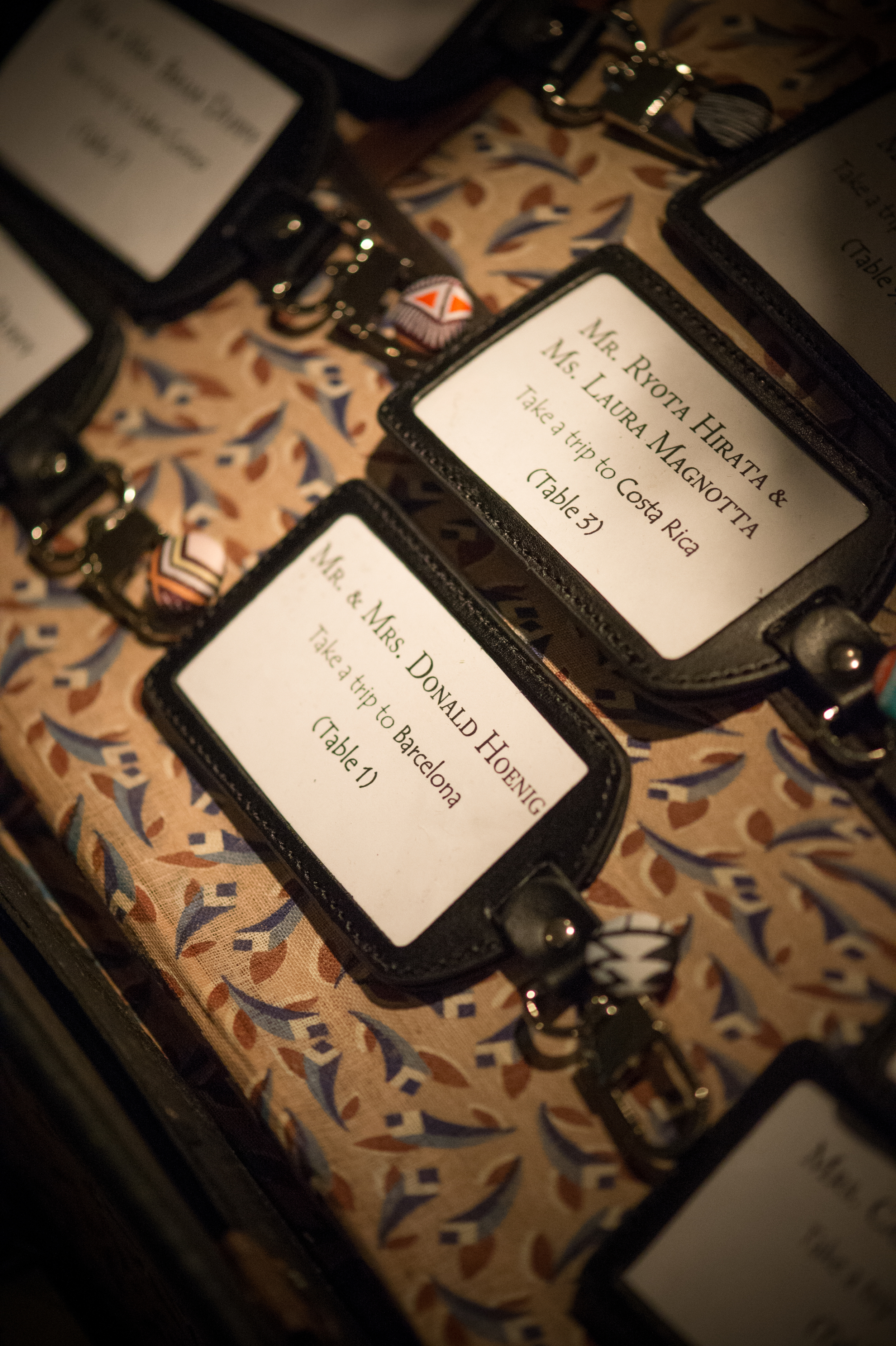 Luggage tag escort cards & favors! Genius! Displayed in a suitcase.