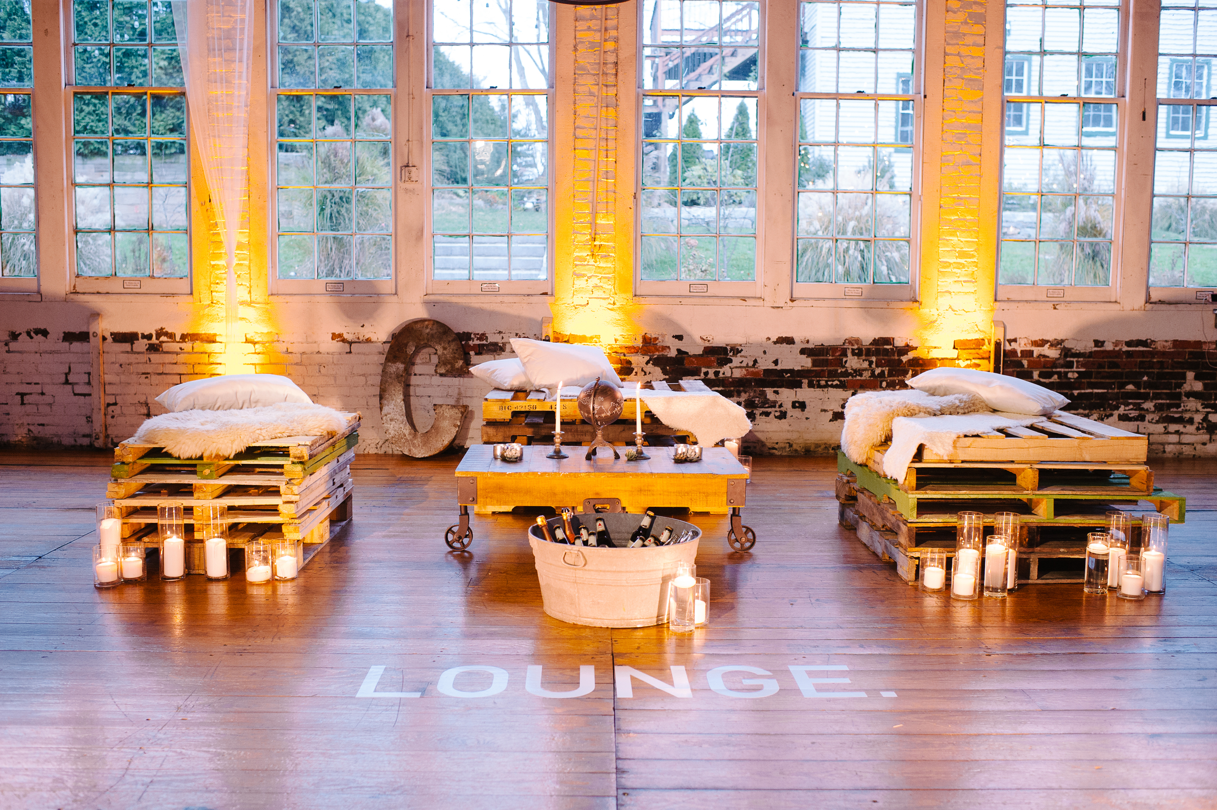 "Shipping pallets are all the rage on Pinterest. I loved the idea of having pallets as ceremony seating and converted into a lounge. Each stack got ""zhoozh-ed"" up with painting one pallet per pile. Soften with real lamb fur & pillows this was actually pretty comfortable."