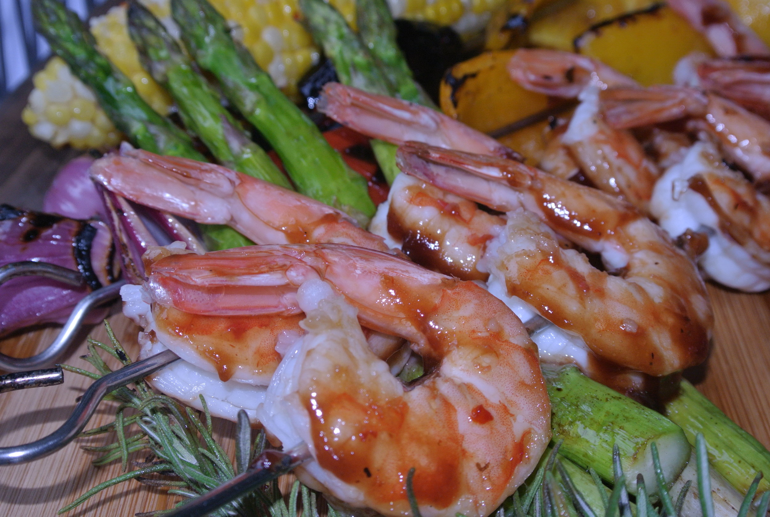 Entree Photos - Featured image: Honey glazed shrimp kabobs with vegetables, served over asparagus