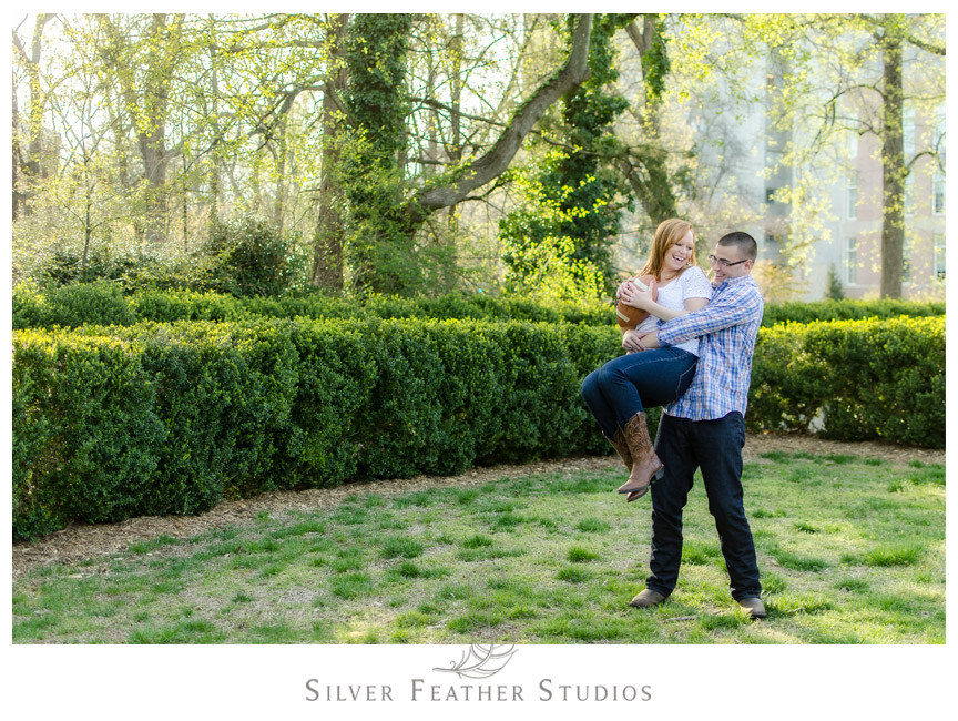 Adam picks up his fiance as they play football at their UNC engagement session.  © Silver Feather Studios, Chapel Hill Wedding Photography and Videography