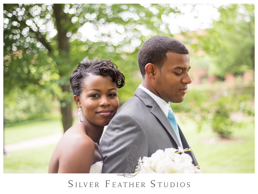 Bride and groom cuddle on the walkways of UNC Greensboro. Photography by Silver Feather Studios.
