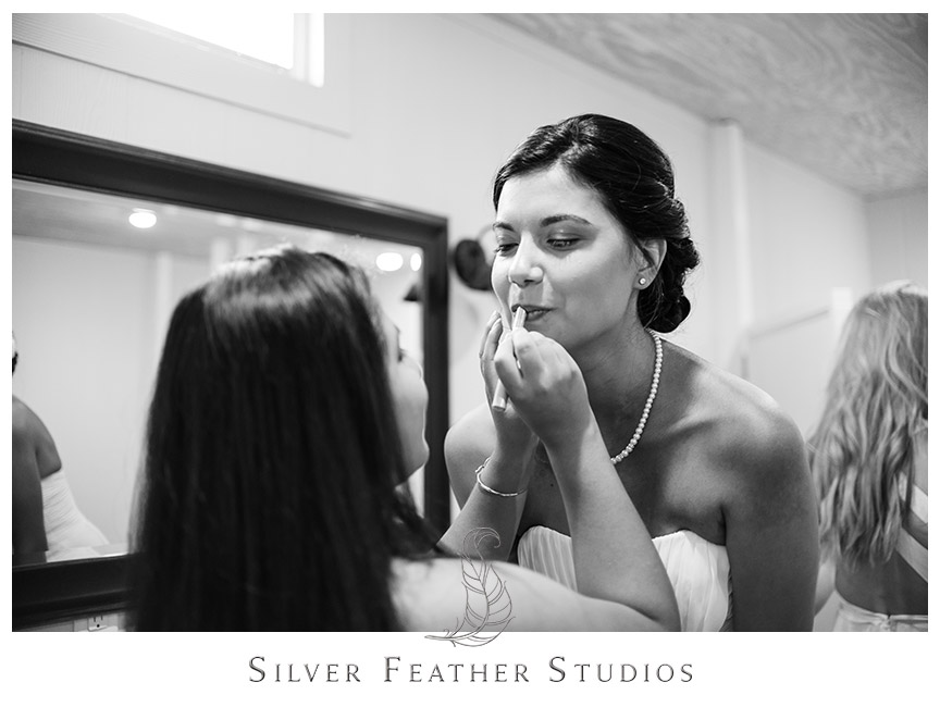 Makeup being put on the bride by her baby sister in this Burlington NC barn wedding. Wedding Photography by Silver Feather Studios.
