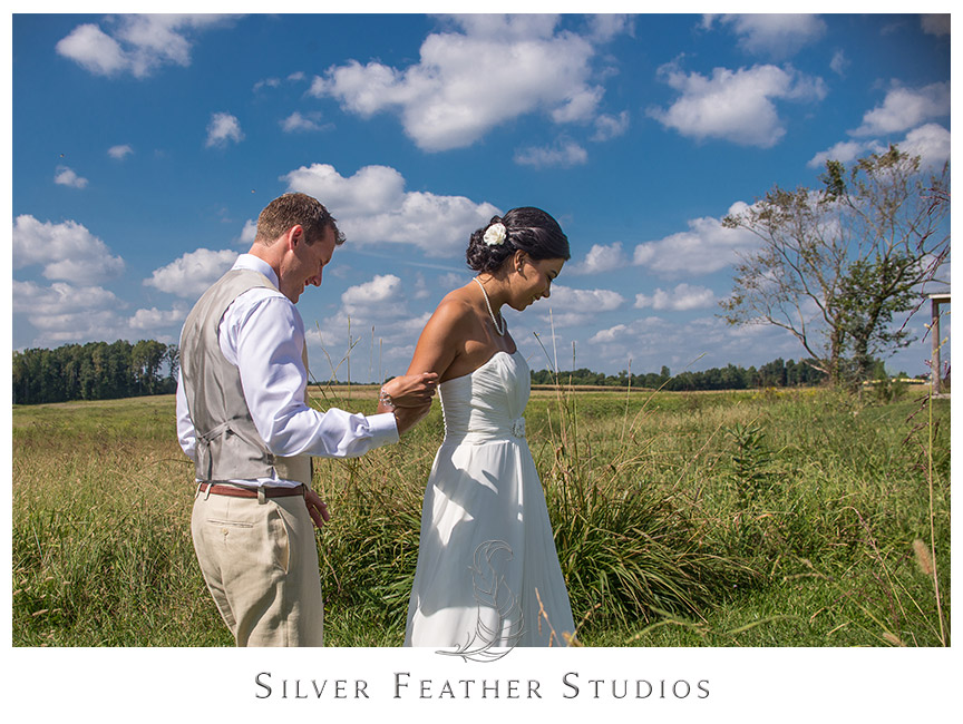 Groom turns his bride during their first look in the grass fields of Starlight Meadows. © Burlington NC Wedding Photographer, Silver Feather Studios