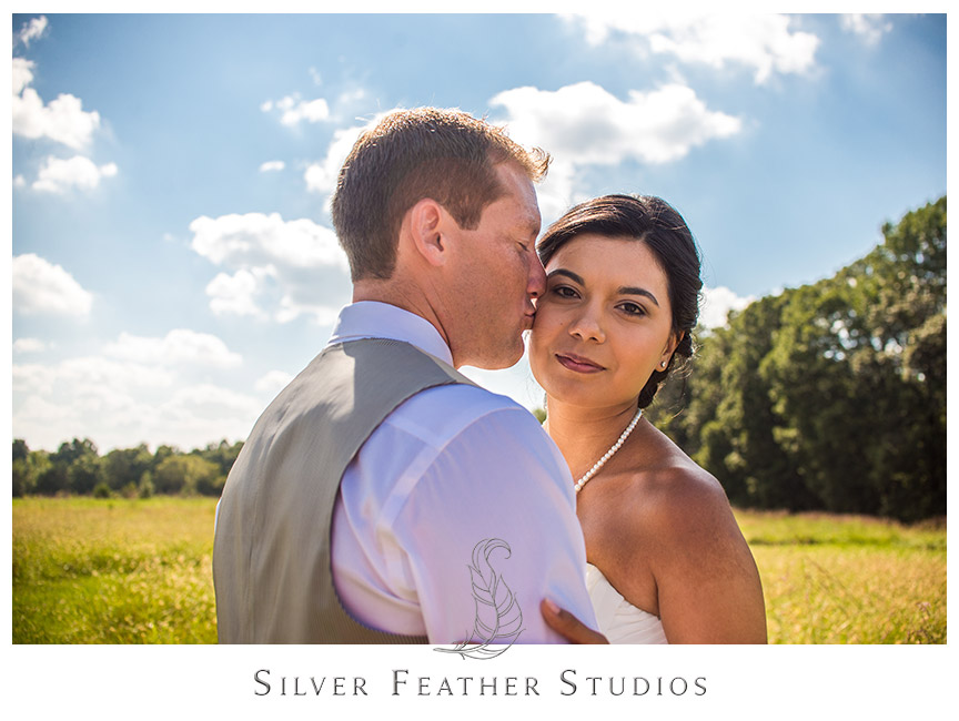 Bride looks amazing in her pearls while the groom kisses her on the check in his beige vest suit. © Burlington Wedding Photographer Silver Feather Studios