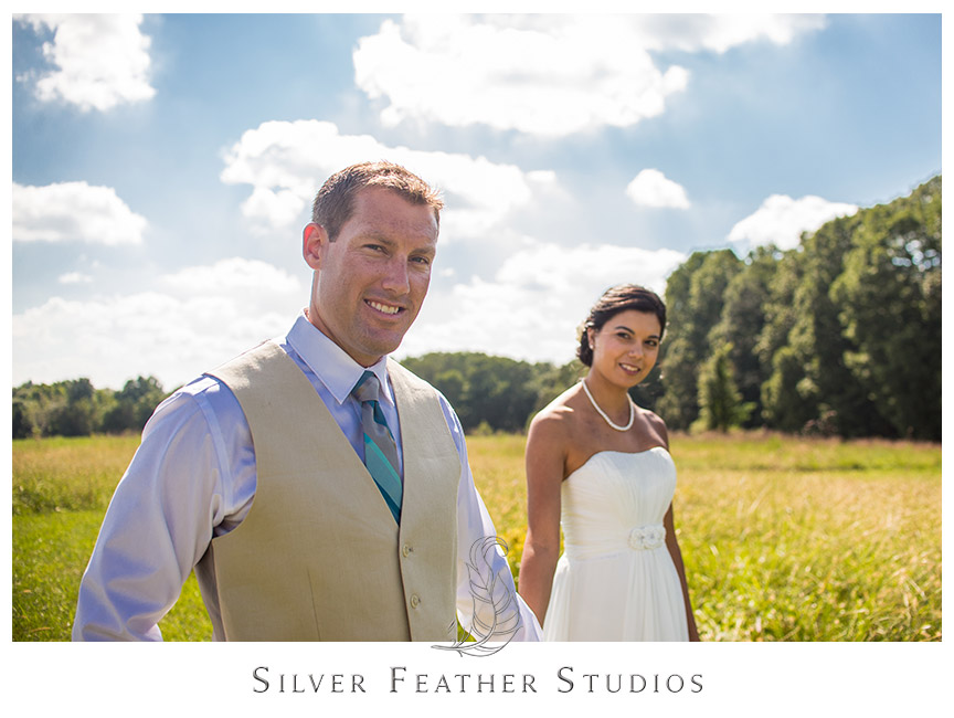 Groom looks fantastic in his beige tux and blue stripe tie, as his beautiful bride trails behind him at Starlight Meadow.  © Silver Feather Studios