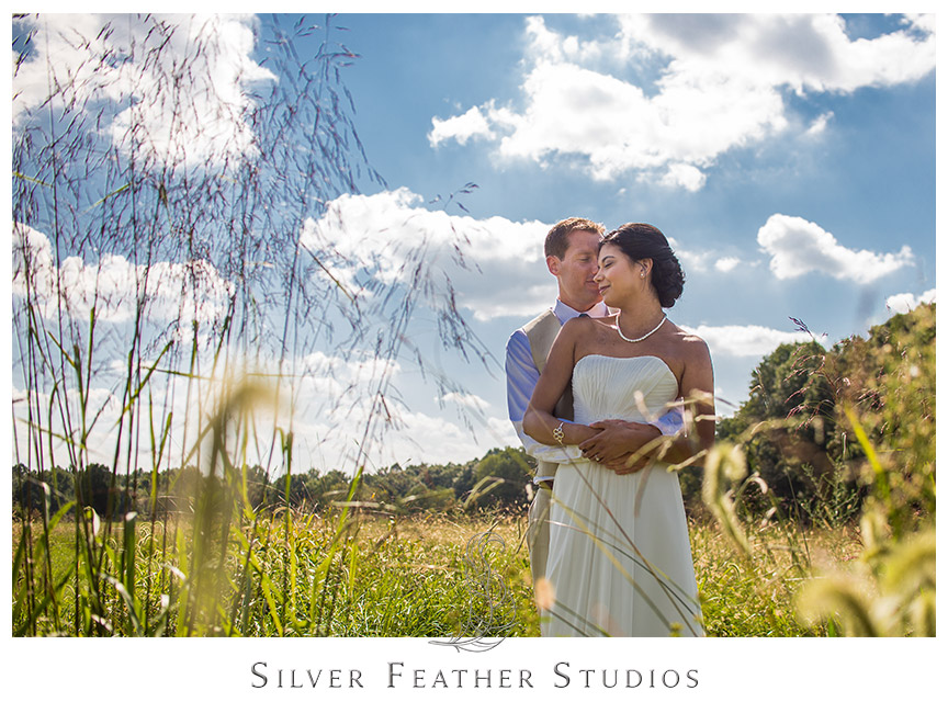 Sweet hug from the bride and groom against a cloudy blue sky in Burlington, North Carolina.   © Silver Feather Studios