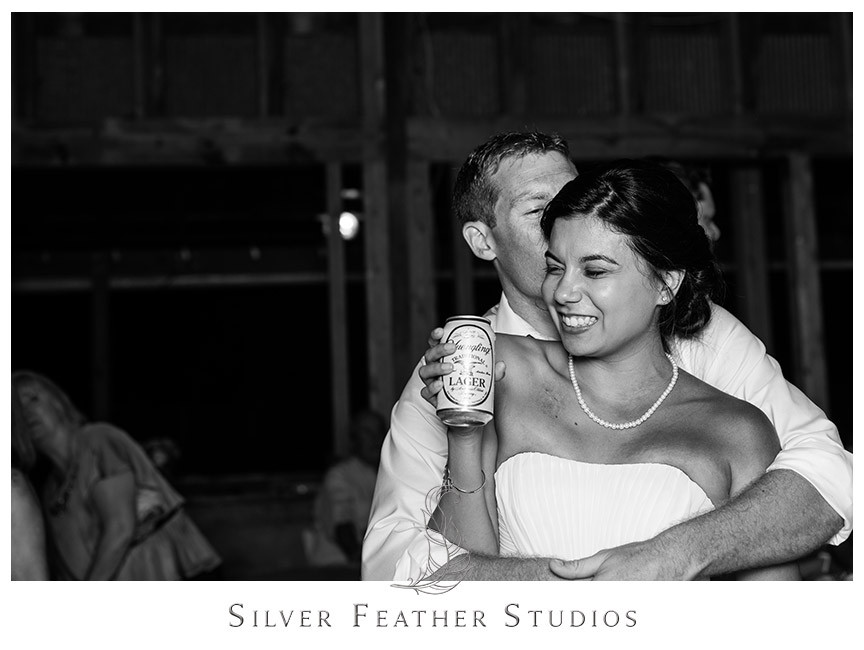 The bride and groom do a final dance at their pink and aqua rustic barn Starlight Meadow wedding.  © Silver Feather Studios, Burlington, NC Wedding Photography