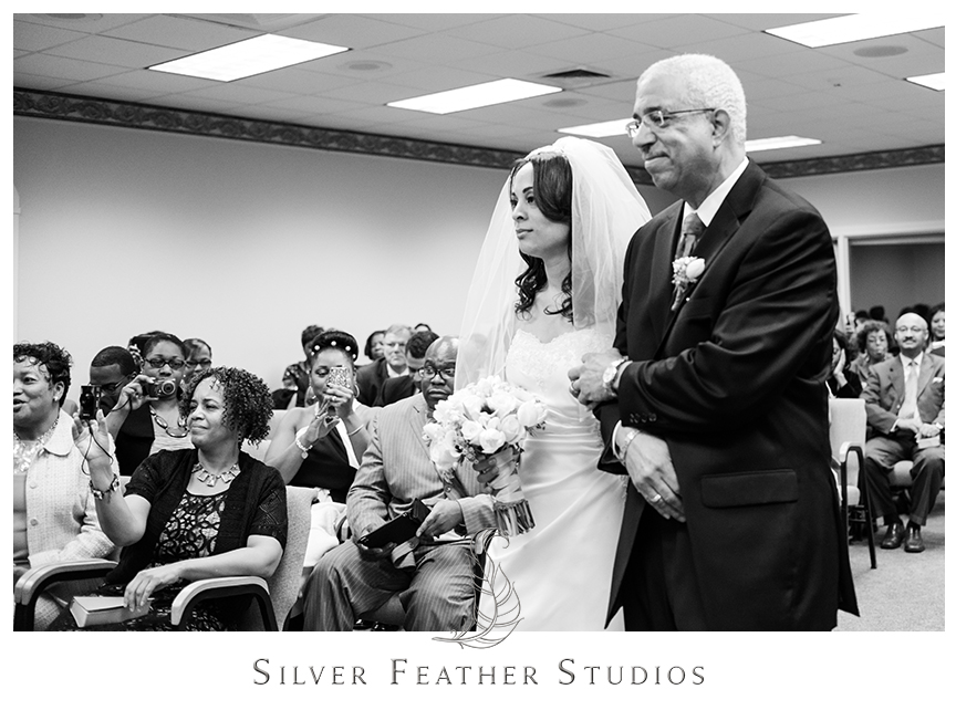 Father walks his daughter down the aisle of the Kingdom Hall of Jehovah's Witnesses. © Silver Feather Studios, Wedding Photography in Greensboro, North Carolina.