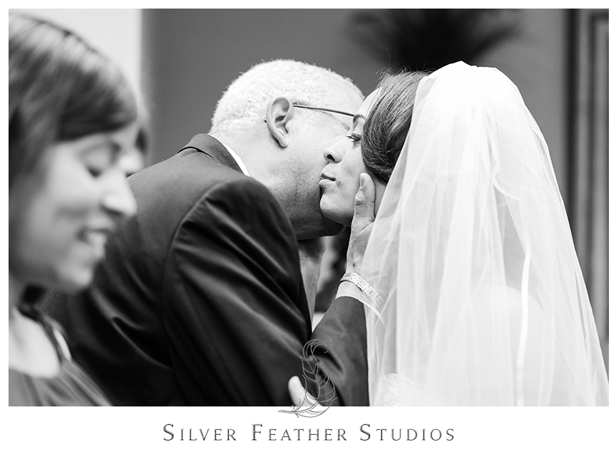 Father kisses his newly married daughter at the Kingdom Hall of Jehovah's Witnesses. © Silver Feather Studios, Wedding Photography in Greensboro, North Carolina.