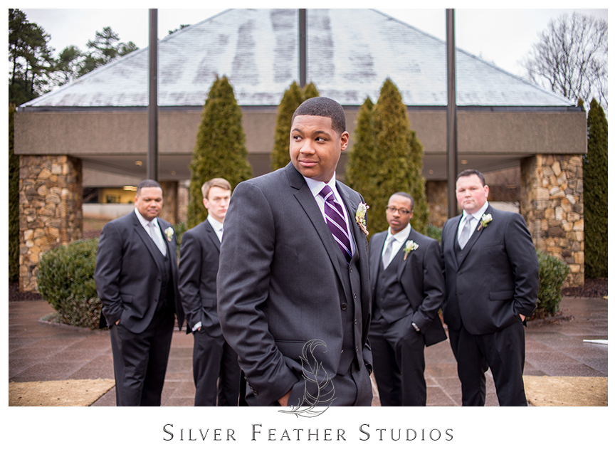 Groomsmen pose in dark grey suits with silver and purple ties at this Bryan Park Golf Center wedding. © Silver Feather Studios, Wedding Photography in Greensboro, North Carolina.