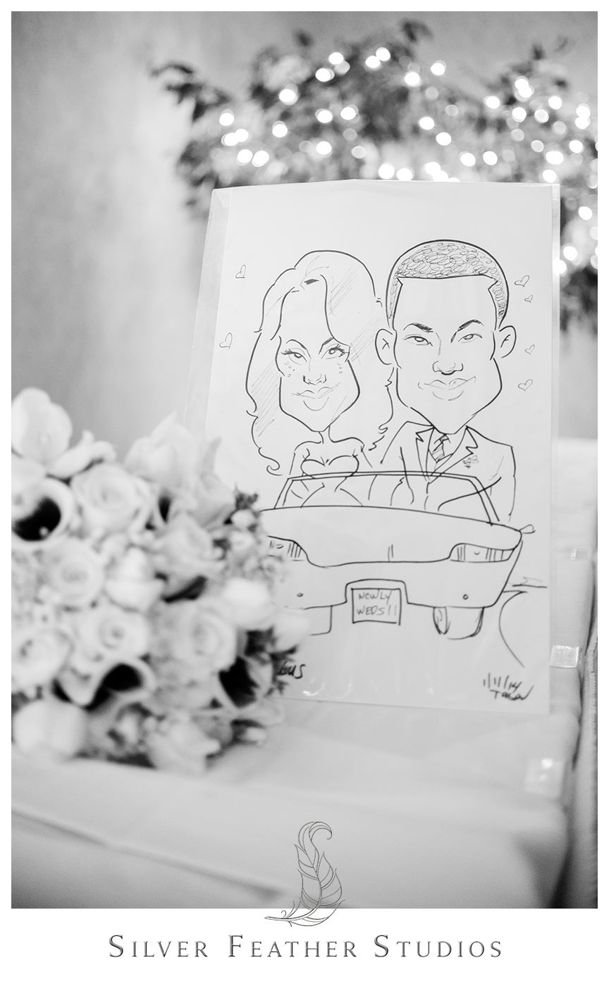 An artist draws a caricature of the bride and groom at their purple and gray Bryan Park Golf Center Wedding reception.© Silver Feather Studios, Wedding Photography in Greensboro, North Carolina.