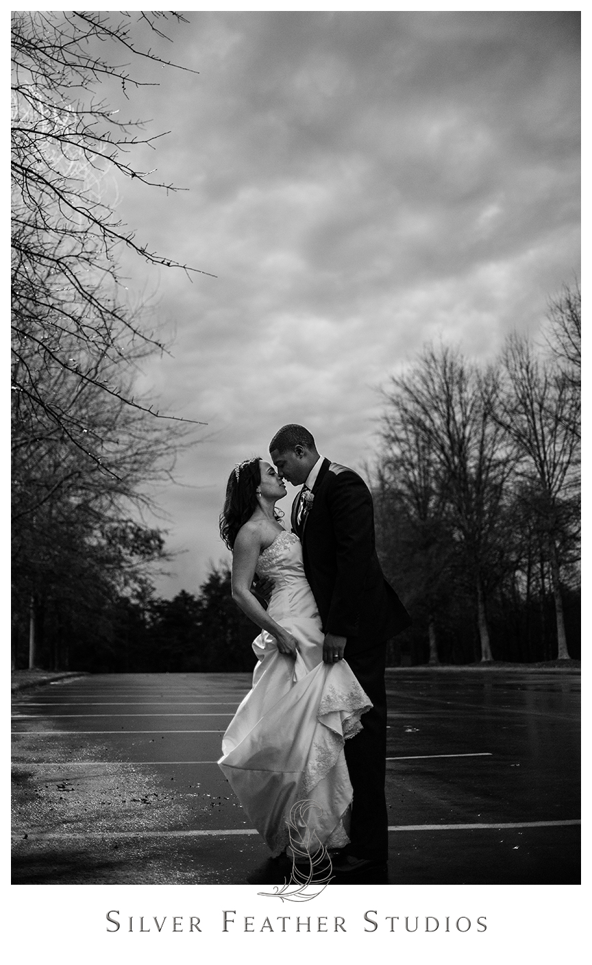 Bride and groom pose in the rain at this purple and gray Bryan Park Golf Center Wedding reception.© Silver Feather Studios, Wedding Photography in Greensboro, North Carolina.