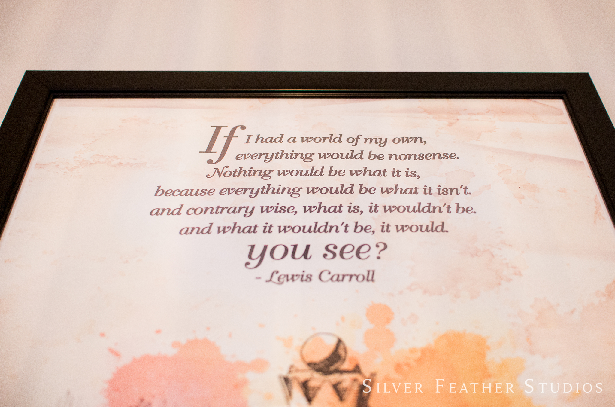 Framed Lewis Carroll quote at this Alice in Wonderland themed wedding event.