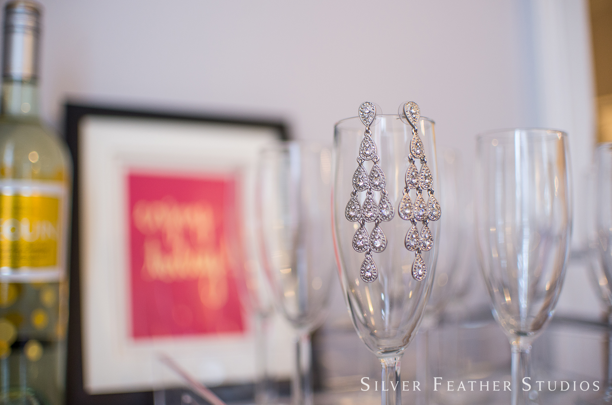 Detail shot of the earrings hanging from a glass at the Mims House, by Raleigh wedding photographer, Silver Feather Studios.