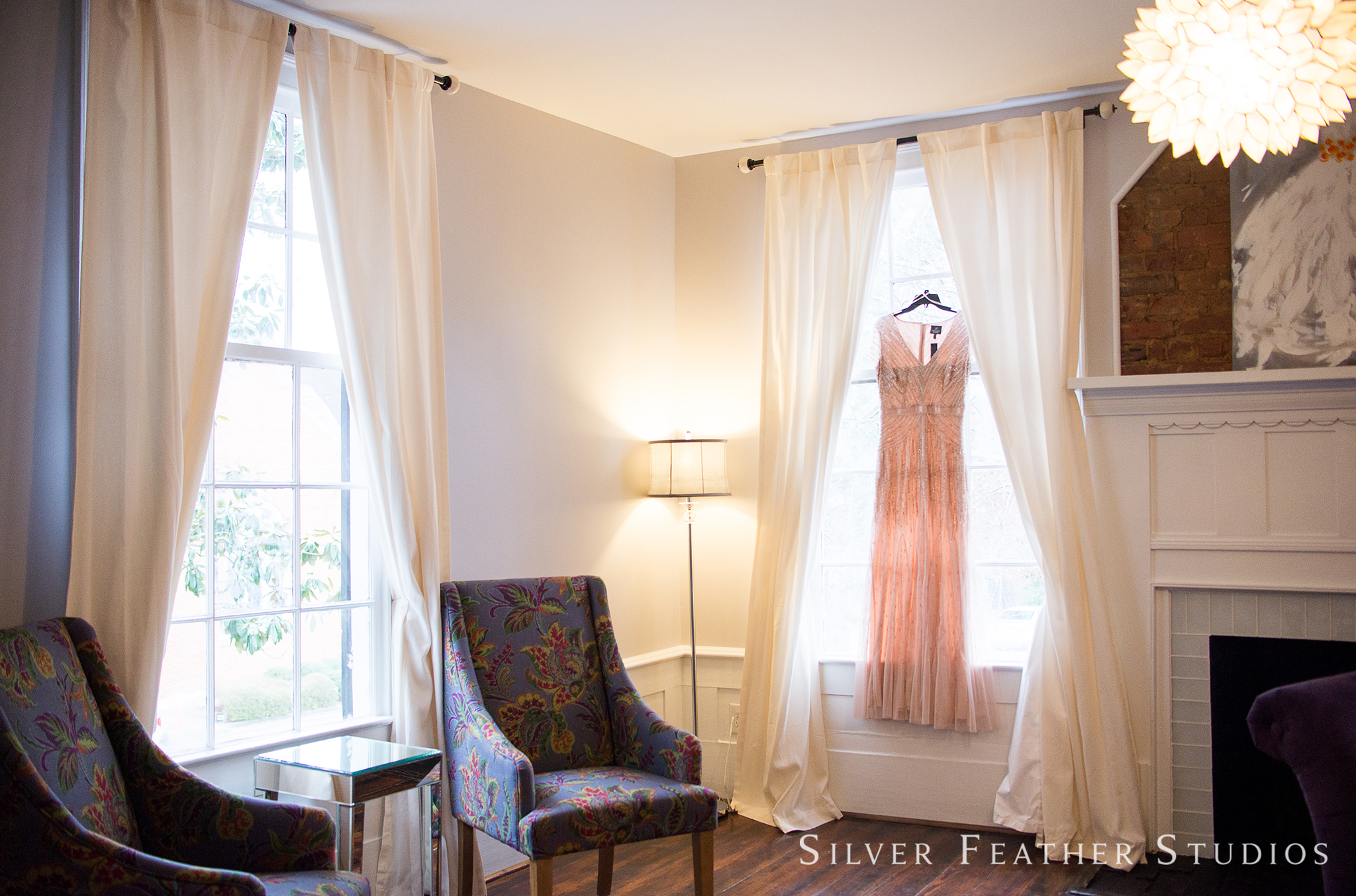 Pink gown hangs from window at this holly springs wedding venue. Raleigh wedding photographer, Silver Feather Studios.