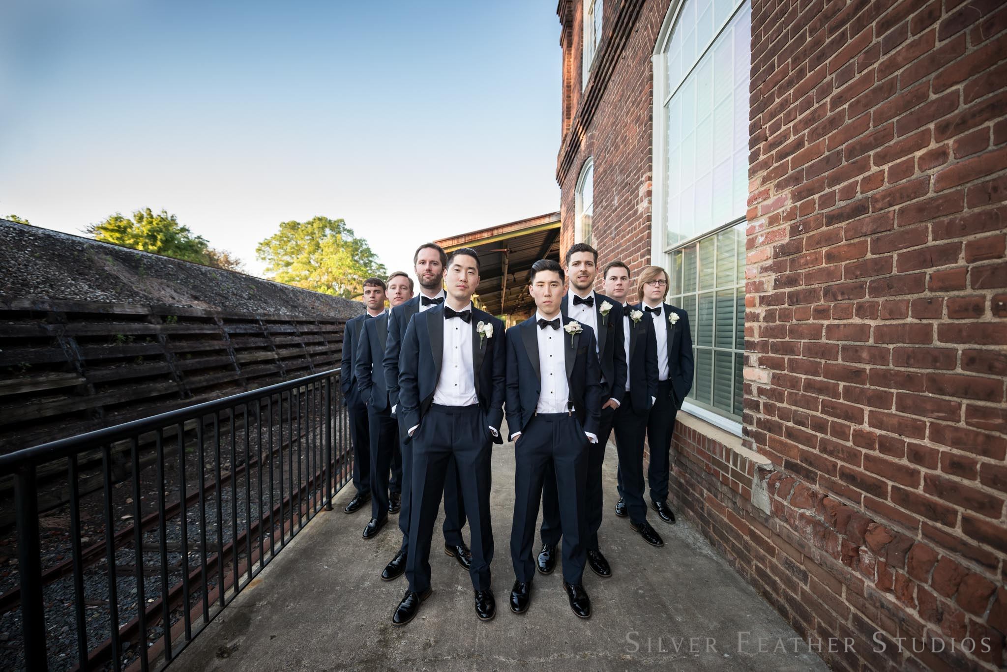 black tuxedo  s with bowties at Jeremy and Anna's classy wedding in Durham. © Silver Feather Studios