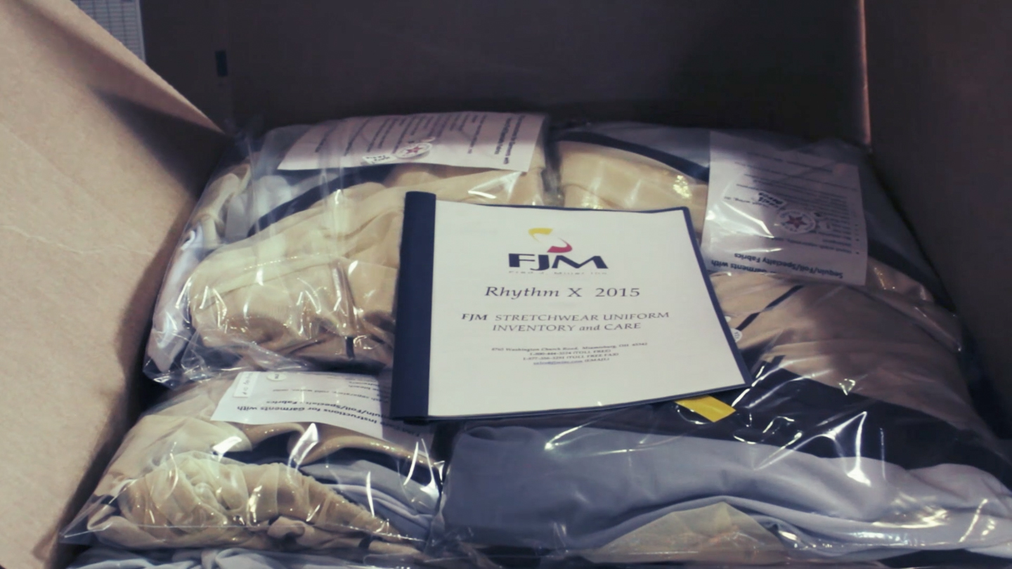 The completed uniforms are packaged with care and fit instructions, ready for pick-up by Rhythm X, Inc.!
