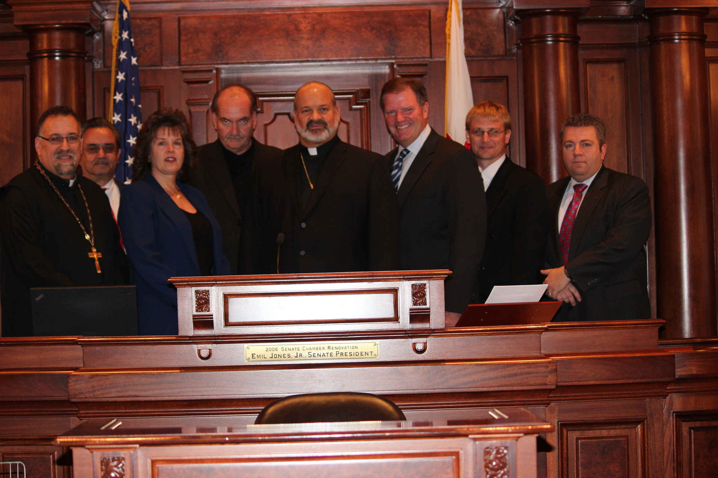At the Senate President's podium  In the Balcony of the Illinois State Capitol. From left to right:Fr. George Pyle (Pastor of St. Anthony, Springfield, IL),Nick Xamis (Pres. Parish Council, St. Anthony GOC, Springfield, IL),Katena andFrank and Lagouros, His Grace Bishop Demetrios, Senator Bill Bradley, John Ackerman, George Vranas (Pres. Parish Council, St. Nicholas GOC,Oak Lawn, IL)