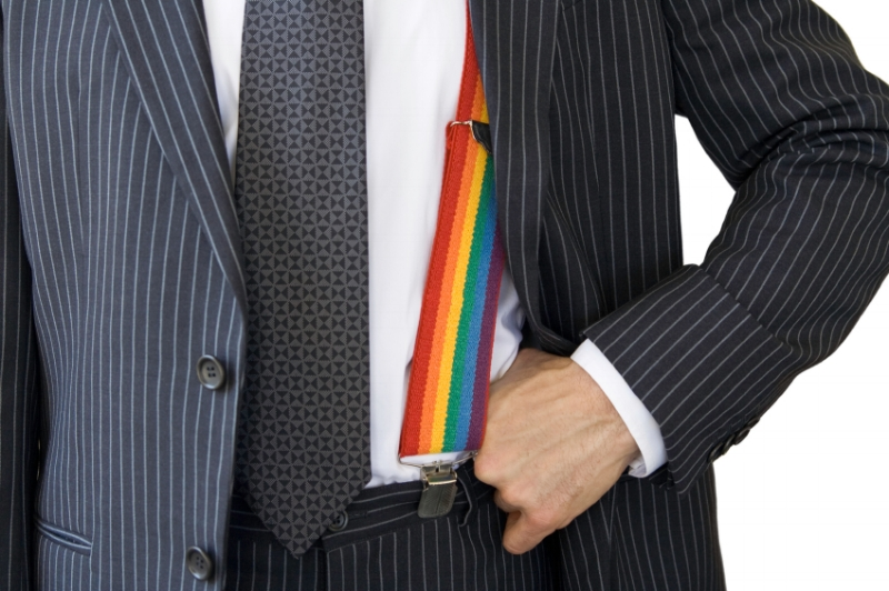 Man in a business suit with a rainbow suspender showing.